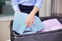 De kleren van de onderneemsterverpakking in reiszak Stock Foto