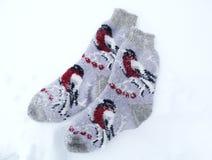 De kleren van de sokkenwinter op sneeuwachtergrond Stock Afbeeldingen