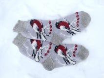 De kleren van de sokkenwinter op sneeuwachtergrond Royalty-vrije Stock Fotografie