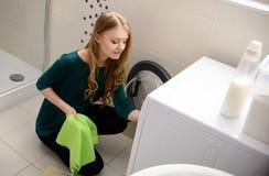 De kleren van de vrouwenlading in wasmachine stock afbeelding