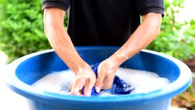 De kleren van de handwas in blauw bassin stock footage
