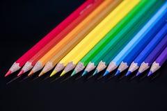 De kleuren van het regenboogpotlood schikten diagonaal op een zwart glas royalty-vrije stock afbeelding