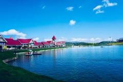 De kleuren van het water en de hemel vullen elkaar aan, en een rij van villa's is gestippeld onder hen stock foto's