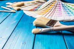 De kleurenpalet van verfblikken, blikken met borstels op blauwe lijst worden geopend die Stock Afbeeldingen