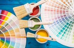 De kleurenpalet van verfblikken, blikken met borstels op blauwe lijst worden geopend die Stock Fotografie