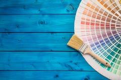 De kleurenpalet van verfblikken, blikken met borstels op blauwe lijst worden geopend die Royalty-vrije Stock Foto