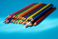 De kleurenpotloden liggen op een blauwe achtergrond in de zon` s stralen royalty-vrije stock fotografie