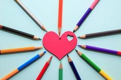De kleurenpotloden schikken binnen in de kleuren van het kleurenwiel rond houten rood hart op blauwe achtergrond stock foto