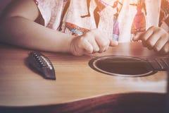 De kleurentoon van de beeldverwerking instagram Close-upkind het spelen gitaar Concept liftstyle, het leren, hobby, musicus, droo Stock Foto