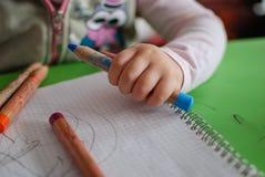 De kleurpotloden van de kindholding Stock Fotografie