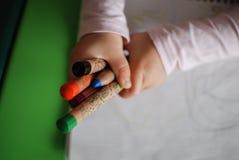 De kleurpotloden van de kindholding Stock Foto