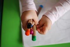 De kleurpotloden van de kindholding Stock Afbeeldingen
