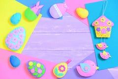 De kleurrijke Achtergrond van Pasen Creatieve gevoelde Pasen-ambachten op gevoelde bladen en op lilac houten achtergrond met exem stock fotografie