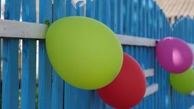 De kleurrijke ballons verfraaien de omheining Feestelijke decoratie van een vakantie van kinderen met ballons, buitenhuis Mooi stock video
