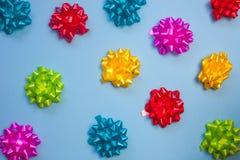 De kleurrijke bogen van het florasatijn op pastelkleur blauwe achtergrond stock afbeelding