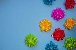 De kleurrijke bogen van het florasatijn op pastelkleur blauwe achtergrond met exemplaar SP royalty-vrije stock foto