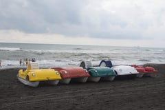 De kleurrijke boten van de pedalopeddel op het strand, bewolking, wolken, golven stock fotografie