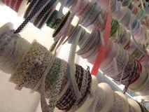 De kleurrijke broodjes van de lintband, die in vertoning bij een kleine winkel hangen stock foto