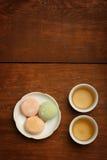 De kleurrijke cake van de mochirijst op witte plaat en porseleinkoppen met Royalty-vrije Stock Afbeeldingen