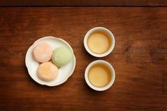 De kleurrijke cake van de mochirijst op witte plaat en twee porseleinkoppen w Royalty-vrije Stock Fotografie