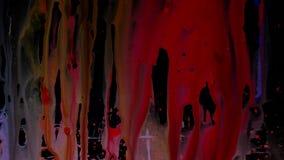 De kleurrijke dia van Inktdruppeltjes op glas Zwarte achtergrond stock videobeelden