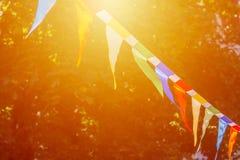 De kleurrijke driehoekige vlaggen van verfraaid vieren openluchtpartijzonlicht royalty-vrije stock afbeelding
