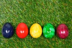De kleurrijke eieren liggen op een synthetisch gras Royalty-vrije Stock Afbeelding