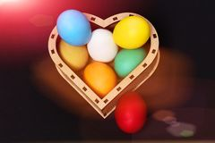 De kleurrijke eieren van Pasen in houten die hartdoos op zwarte wordt geïsoleerd Stock Afbeelding