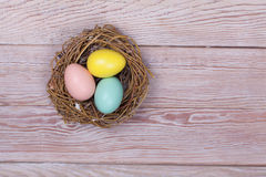 De kleurrijke eieren van Pasen in vogelnest op houten achtergrond Royalty-vrije Stock Fotografie