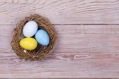 De kleurrijke eieren van Pasen in vogelnest op houten achtergrond Royalty-vrije Stock Afbeelding