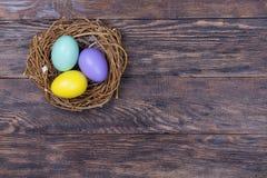 De kleurrijke eieren van Pasen in vogelnest op houten achtergrond stock fotografie