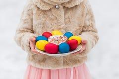 De kleurrijke eieren voor Pasen-vakantie in handen op een plaat sluiten omhoog Royalty-vrije Stock Afbeelding