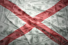 De kleurrijke golvende vlag van de staat van Alabama op een Amerikaanse achtergrond van het dollargeld Stock Foto's