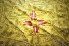 De kleurrijke golvende vlag van de staat van New Mexico op een Amerikaanse achtergrond van het dollargeld royalty-vrije stock fotografie