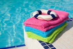 De kleurrijke handdoeken en de reddingsboei dichtbij zwemmen pool Stock Foto