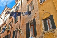 De kleurrijke hoeken van Venetië met oude gebouwen en schilderachtige de bouwvoorgevel met vensters en kleren die tussen ho hange stock foto's