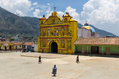 De kleurrijke kerk van San Andres Xecul en het lokale Mayan vrouw drie lopen op de straat in Guatemala Royalty-vrije Stock Afbeelding