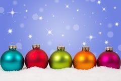 De kleurrijke Kerstmisballen speelt op een rij achtergronddecoratie mee Stock Fotografie