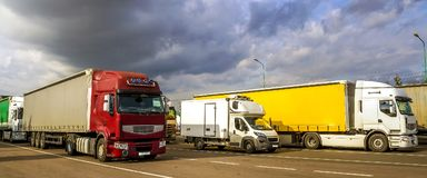 De kleurrijke moderne grote semi-vrachtwagens en de aanhangwagens van verschillend maken stock afbeelding