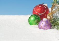 De kleurrijke ornamenten van Kerstmis in sneeuw Royalty-vrije Stock Foto's