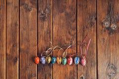 De kleurrijke paaseieren, geschilderde hand, schikten in een lijn met ruimte op de bovenkant op een uitstekende houten lijst stock afbeelding
