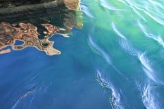 De kleurrijke patronen van blauw, bruin en wit worden gezien in bezinningen in het water van een meer Royalty-vrije Stock Fotografie