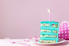 De kleurrijke plak van de verjaardagscake met kaars Royalty-vrije Stock Afbeeldingen