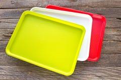 De kleurrijke platen van het middagmaal plastic vierkante voedsel op houten backgrou stock foto's