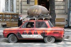 De kleurrijke retro Sovjet rode auto met artistiek beelden en een kruik op het dak aan pret en trekken aandacht bij de ingang aan stock foto