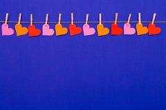 De kleurrijke slinger van de Hartvorm op blauwe achtergrond Royalty-vrije Stock Fotografie
