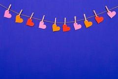 De kleurrijke slinger van de Hartvorm op blauwe achtergrond Stock Afbeeldingen