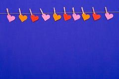 De kleurrijke slinger van de Hartvorm op blauwe achtergrond Royalty-vrije Stock Foto's