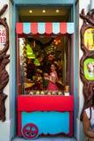 De kleurrijke sprookjes als thema hebben shopfront decoratie van zoete winkel met mooie jonge dameverkoper in roze kleding Stock Foto