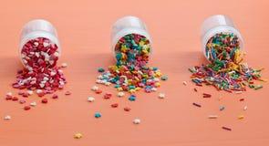 De kleurrijke suiker bestrooit verspreid op een houten lijst Stock Foto's